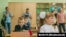 NOVOKUZNETSK, KEMEROVO REGION, RUSSIA: First-grade students and teacher are in school classroom at first lesson - vthe day of knowledge in Russia. September 2, 1014