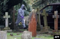 A man in a hazmat suit walks by London Road Cemetery in Salisbury, England, near the home of Sergei Skripal, who, along with his daughter Yulia were poisoned with Novichok on March 4, 2018.
