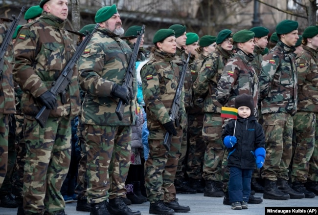 LITHUANIA -- A boy stands near Lithuanian soldiers during a celebration of Independence day at Independence Square, in front of the Parliament Palace in Vilnius, March 11, 2019