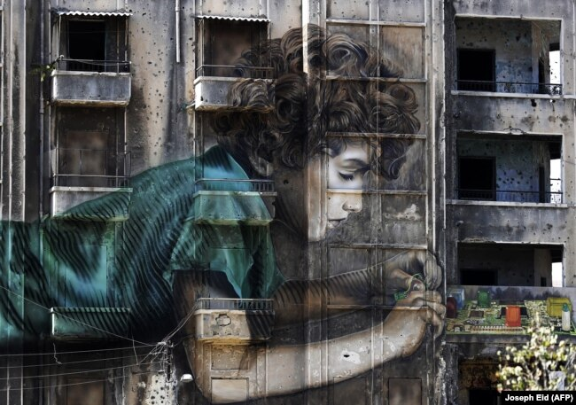 LEBANON -- Graffiti of a boy working on an electronic device is seen on a building riddled with holes from shrapnel dating back from the Lebanese civil war (1975-1990) in Beirut on Sep 26, 2017 AFP JOSEPH EID