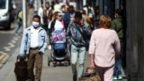 People walk down a street following the coronavirus disease (COVID-19) outbreak, in Ilford, London, Britain July 29, 2020.
