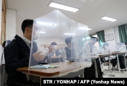 South Korean students sit behind protective shields as a preventative measure against the COVID-19 novel coronavirus in a classroom in Daejeon on May 20, 2020.