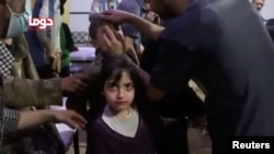 A girl looks on following alleged chemical weapons attack, in what is said to be Douma, Syria in this still image from video obtained by Reuters on April 8, 2018. White Helmets/Reuters TV