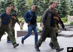 "UKRAINE – Aleksandr Borodai, Russian citizen and ""Prime Minister"" of the self proclaimed ""Donetsk People's Republic"", center, walks accompanied by pro-Russian fighters in Donetsk, eastern Ukraine, July 20, 2014"