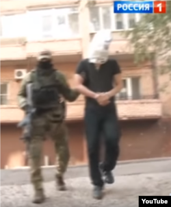 "Oleksandr Pogorelov, who allegedly assassinated separatist fighter Oleksandr ""Motorola"" Pogorelov, led out for the caemras. (Screengrab from ""News of the Week with Dmitry Kisleyov, Rossiya 1)."