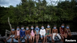 Children wearing protective face masks as healthcare workers visit to check on residents during the COVID-19 outbreak in the municipality of Portel, Marajo island, Para state, Brazil, June 13, 2020. REUTERS/Ueslei Marcelino