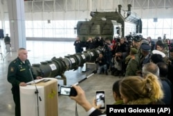 RUSSIA -- Lt. Gen. Mikhail Matveevsky, the chief of the military's missile and artillery forces, left, speaks during a briefing by the Russian Defense Ministry, as the 9M729 land-based cruise missile, center, is displayed near its launcher.