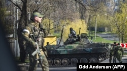 Pro-Russian separatist soldiers stand next to a vehicle as they close off a road in Donetsk