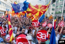 "MACEDONIA -- People wave Macedonian and Europan flags as they attend a campaign rally for the ""yes"" ahead of a referendum on wether to change the country's name to ""Republic of Northern Macedonia"", in Skopje on September 16, 2018."