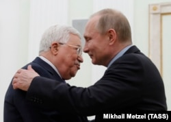 RUSSIA -- Russian President Vladimir Putin embraces Palestinian President Mahmoud Abbas during a meeting at the Kremlin in Moscow, February 12, 2018.