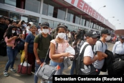 Peru - People wearing face masks wait to board a bus at a bus station after Peru's government deployed military personnel to block major roads, as the country rolled out a 15-day state of emergency to slow the spread of coronavirus disease (COVID-19).