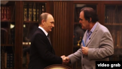 "A view grab from 2017's ""The Putin Interviews"", showing U.S. director Oliver Stone shaking hands with Russian President Vladimir Putin. Stone recently interviewed Putin again for his latest film, ""Revealing Ukraine""."