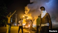 U.S. -- Demonstrators stand in the middle of a St.Louis area street as they react to tear gas fired by police during ongoing protests in reaction to the shooting of teenager Michael Brown, near Ferguson, Missouri, August 18, 2014.