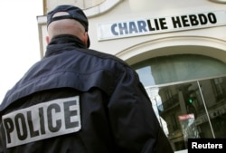 A policeman stands guard outside the French satirical weekly Charlie Hebdo in Paris, Feb. 9, 2006, after the publication reprinted cartoons of the Prophet Muhammad and published one of its own on its front page.