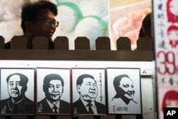 A man stands near a series of paper cuttings depicting Chinese President Xi Jinping next to former Chinese leader Mao Zedong and Deng Xiaoping. This photo was taken on March 1, 2018, in Shanghai.