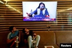 Iraqi youth watch the news of Islamic State leader Abu Bakr al-Baghdadi's death