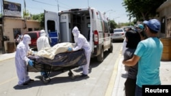 MEXICO – Paramedics transport the body of a man who died from COVID-19 in Ciudad Juarez, on May 26, 2020.