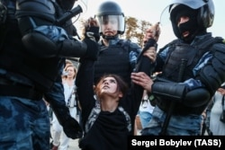 RUSSIA – MOSCOW, JULY 27, 2019: Police officers detain a woman during a protest on Trubnaya Square against against the banning of opposition candidates from Moscow municipal elections set for September 8.