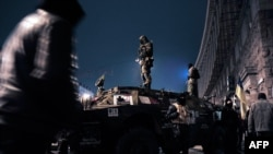 Ukraine -- Maidan self-defence activists stand on an armored vehicle in central Kyiv, February 23, 2014