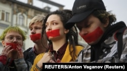 RUSSIA -- Activists from the local LGBT community put tape over their mouths while walking during a protest against discrimination in St. Petersburg, April 17, 2019