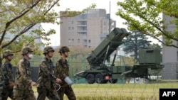PAC-3 missile launchers shown in background, Tokyo, April 9, 2013. Japan plans to deploy an additional missile defense system, Aegis Ashore, by 2023.