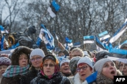 People wave Estonian flags in front of the Estonian Parliament during a festive ceremony to celebrate 100 years since Estonia declared independence for the first time in 1918, in Tallinn on February 24, 2018. / AFP PHOTO / Raigo Pajula