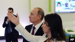 Russian President Vladimir Putin and RT's Editor-in-Chief of RT Margarita Simonyan attend an exhibition marking RT's 10th anniversary in Moscow, December 10, 2015.