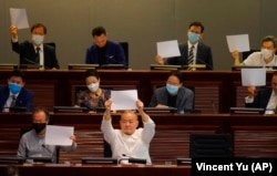 Pro-democracy lawmakers raise white papers to protest during a meeting to discuss the new national security law at the Legislative Council on July 7, 2020. AP/Vincent Yu