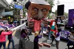 Activists destroy an effigy of Duterte during a rally near the Malacanang presidential palace to mark International Women's Day on Monday, March 8, 2021 in Manila.