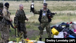UKRAINE – A pro-Russian fighter holds up a toy found among the debris at the crash site of a Malaysia Airlines jet near the village of Hrabove, Donetsk region, July 18, 2014