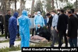 Virus Outbreak Mideast Iran -- Relatives mourn over the body of Fatemeh Rahbar, a lawmaker-elect from a Tehran constituency, who died on Saturday after being infected with the new coronavirus, at Behesht-e-Zahra cemetery, just outside Tehran, Iran, Sunday