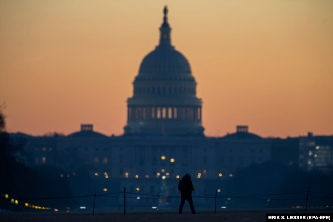 U.S. -- A man walks on the National Mall in front of the U.S. Capitol building at dawn in Washington, DC, U.S., December 27, 2018