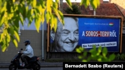 HUNGARY -- FILE PHOTO: A man rides his moped past a government billboard displaying George Soros amid accusations he was trying to bring in immigrants.