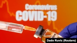 "FILE PHOTO: A small bottle labeled with a ""Vaccine"" sticker is held near a medical syringe in front of displayed ""Coronavirus COVID-19"" words in this illustration taken April 10, 2020."