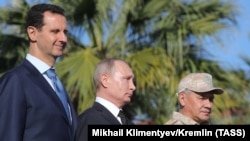SYRIA -- (Left to right) Syrian President Bashar al-Assad, Russian President Vladimir Putin and Russian Defense Minister Sergei Shoigu visit the Hmeimim military base in Latakia Province, December 11, 2017