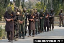 AFGHANISTAN -- Forces with Afghanistan's National Directorate Security (NDS) escort alleged Taliban fighters after they are presented to media in Jalalabad, January 23, 2019