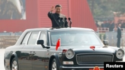 Chinese President Xi Jinping waves from a vehicle as he reviews the troops at a military parade marking the 70th founding anniversary of People's Republic of China, on its National Day in Beijing, China October 1, 2019.