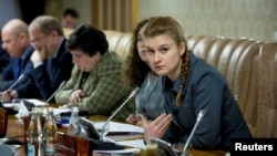 RUSSIA - Public figure Maria Butina (right) attends a meeting of a group of experts, affiliated with the government of Russia, in this undated handout photo obtained by Reuters on July 17, 2018