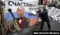 UKRAINE – A pro-European integration supporter washes a banner with an image of Russian President Vladimir Putin near a barricade in Independence Square where the supporters are holding a rally, in Kyiv January 9, 2014