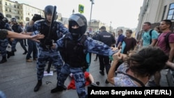 Russia -- Riot police use batons during an opposition rally in Moscow on July 27, 2019. Thousands of people took to the streets to protest the banning of opposition candidates from municipal elections set for September 8.