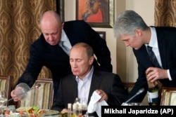 RUSSIA -- Businessman Yevgeny Prigozhin, left, serves food to Russian Prime Minister Vladimir Putin, center, during dinner at Prigozhin's restaurant outside Moscow, November 11, 2011