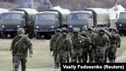 UKRAINE – Uniformed men, believed to be Russian servicemen, walk in formation near a Ukrainian military base in the village of Perevalnoye outside Simferopol, March 6, 2014