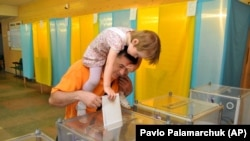 UKRAINE – An voter with his daughter casts his ballot at a polling station during presidential elections in Lviv, May 25, 2014.