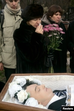 Russia -- Nataliya Magnitskaya (L), mother of Sergei Magnitsky, grieves over her son 's body during his funeral at a cemetery in Moscow, November 20, 2009