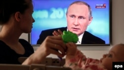 Russia -- A Russian woman plays with her baby while watching the televised call-in show with President V;adimir Putin. in Moscow, April 14, 2016.