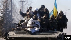 Ukraine -- Ukrainian soldiers ride an armoured personnel carrier (APC) as they leave the eastern Ukrainian city of Debaltseve, 18Feb2015