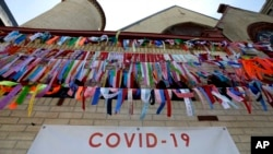 Ribbons hang in remembrance of victims of the coronavirus pandemic outside the Grant African Methodist Episcopal Church, Tuesday, May 19, 2020, in Boston. (AP Photo/Steven Senne)