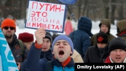 "RUSSIA – Truck driver holding a sign ""Putin is war and poverty"" during a protest in St.Petersburg, Feb. 6, 2016"