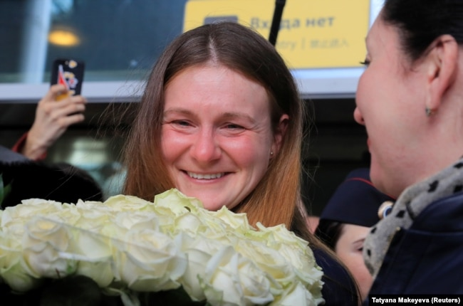 RUSSIA -- Convicted Russian agent Maria Butina, who was released from a Florida prison and then deported by U.S. immigration officials, holds flowers upon her arrival at Sheremetyevo International Airport outside Moscow, Russia Octo