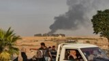 Syrians ride a pickup truck past smoke as Arab and Kurdish civilians flee following Turkish bombardment on Syria's northeastern town of Ras al-Ain in the Hasakeh province along the Turkish border on October 9, 2019.